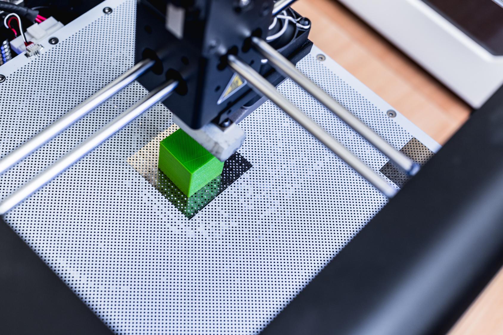 3D Drucker in Aktion beim Druck eines grünen Würfels